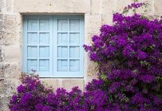 Vieille façade avec la fenêtre bleue et les fleurs pourpres images libres de droits