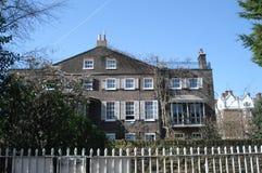 Vieille façade de bâtiment résidentiel avec les fenêtres et le jardin de ceinture blancs multiples photos libres de droits