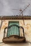 Vieille façade de maison avec le balcon rouillé et les abat-jour verts Photo stock
