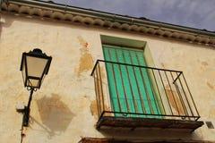 Vieille façade de maison avec le balcon rouillé et les abat-jour verts Image libre de droits