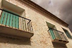 Vieille façade de maison avec le balcon rouillé et les abat-jour verts Photos libres de droits