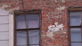 Vieille façade de maison avec le mur de briques et les couples des fenêtres en journée banque de vidéos