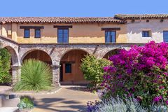 Vieille façade de maison d'Adobe avec des fenêtres photos stock