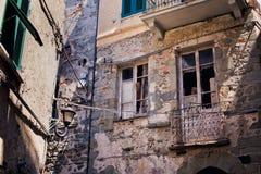 Vieille façade rocailleuse italienne de bâtiment avec des fissures et des abat-jour en bois ruinés Vieux style italien traditionn image stock