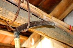 Vieille faux accrochant sur un toit en bois Comcept d'agriculture images libres de droits