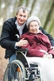 Vieille femme aînée dans le fauteuil roulant avec le fils prudent Image libre de droits
