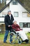Vieille femme aînée dans le fauteuil roulant avec le fils prudent Image stock