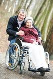 Vieille femme aînée dans le fauteuil roulant avec le fils prudent Photographie stock libre de droits