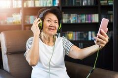 Vieille femme asiatique à l'aide du smartphone pour écouter la musique avec le headpho Photos libres de droits