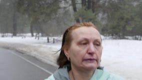 Vieille femme caucasienne supérieure courant en parc neigeux en hiver ?troitement d'avance suivre le tir Mouvement lent clips vidéos