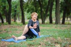 Vieille femme heureuse de yoga Dame mûre de sourire sur un tapis sur un fond de parc Concept sain de style de vie Copiez l'espace Photographie stock libre de droits