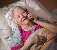 Vieille femme malade se situant dans le lit et à l'aide du téléphone intelligent Photographie stock