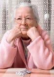 Vieille femme triste avec des pilules à la maison Photographie stock