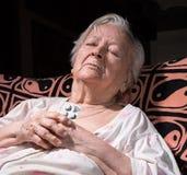 Vieille femme triste tenant des pilules Photographie stock libre de droits