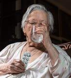 Vieille femme triste tenant des pilules Photo stock