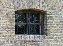 Vieille fenêtre à rénover avec des barres sur un mur de briques jaune Image stock