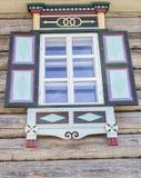 Vieille fenêtre avec avec les volets brillamment peints en verre avec un ciel bleu sur le fond du mur en bois du rondin h de camp Images libres de droits