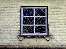 Vieille fenêtre avec le gril sur le mur de briques Photographie stock libre de droits