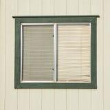 Vieille fenêtre avec les abat-jour de fenêtre en plastique avec les murs en bois Images stock