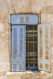 Vieille fenêtre avec les abat-jour rouillés bleus en métal Photographie stock