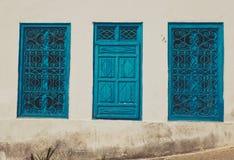 Vieille fenêtre avec les volets bleus sur le mur blanc sale Photo stock