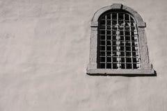 Vieille fenêtre avec un trellis de fer sur une façade de maison Photographie stock