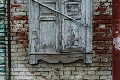 Vieille fenêtre blanche en bois détruite par temps Mur de briques et tuyaux rouillés image stock