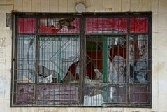 Vieille fenêtre cassée avec un gril sur un mur gris Photo stock