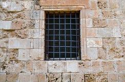 Vieille fenêtre dans le mur de château avec un trellis photos stock