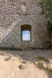 Vieille fenêtre de château avec l'arbre près de la pierre Nuages à l'intérieur de la fenêtre Photo libre de droits