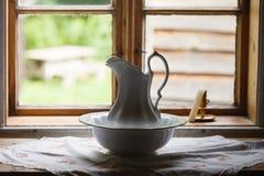 Vieille fenêtre de vintage, cruche en céramique dans le premier plan Images stock