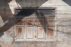 Vieille fenêtre en bois sur le mur antique de ciment avec la lumière et l'ombre Image stock