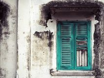 Vieille fenêtre en bois verte et mur blanc du bâtiment photographie stock libre de droits