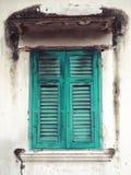 Vieille fenêtre en bois verte et mur blanc du bâtiment photographie stock