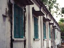 Vieille fenêtre en bois verte et mur blanc du bâtiment images stock