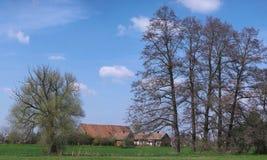 Vieille ferme sous des arbres Image stock