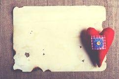 Vieille feuille de vintage de papier et coeur rouge de textile sur la toile de jute, fond de toile à sac Rétros effets de concept Photos libres de droits
