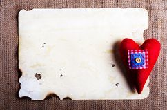 Vieille feuille de vintage de papier et coeur rouge de textile sur la toile de jute, fond de toile à sac Rétros effets de concept Image stock