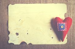 Vieille feuille de vintage de papier et coeur rouge de textile sur la toile de jute, fond de toile à sac Rétros effets de concept Photographie stock