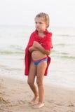 Vieille fille de cinq ans congelée enveloppée dans un T-shirt adulte se tenant sur le bord de mer Images libres de droits