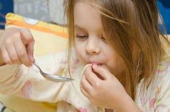 Vieille fille de cinq ans drôle mangeant des spaghetti se reposant dans la huche Image stock