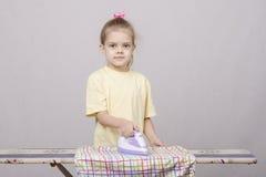 Vieille fille de cinq ans frottant des feuilles Image libre de droits