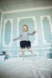 Vieille fille de cinq ans heureuse sautant sur le lit Photographie stock libre de droits