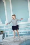 Vieille fille de cinq ans heureuse sautant sur le lit Photo libre de droits