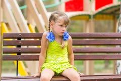 Vieille fille de cinq ans offensée s'asseyant sur le banc et pleurer Images libres de droits