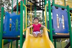 Vieille fille de deux ans chinoise asiatique sur une glissière dans le terrain de jeu photos libres de droits