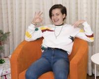 vieille fille 15 an s'asseyant dans un sourire orange de chaise Photographie stock libre de droits