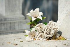 Vieille fleur fausse blanche sur la tombe photographie stock