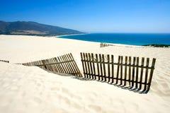Vieille frontière de sécurité collant hors des dunes abandonnées de plage sablonneuse Photographie stock libre de droits