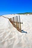 Vieille frontière de sécurité collant hors des dunes abandonnées de plage sablonneuse photographie stock